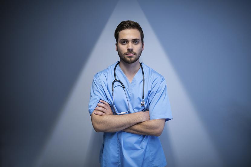 Manlig läkare stående i ljus triangel