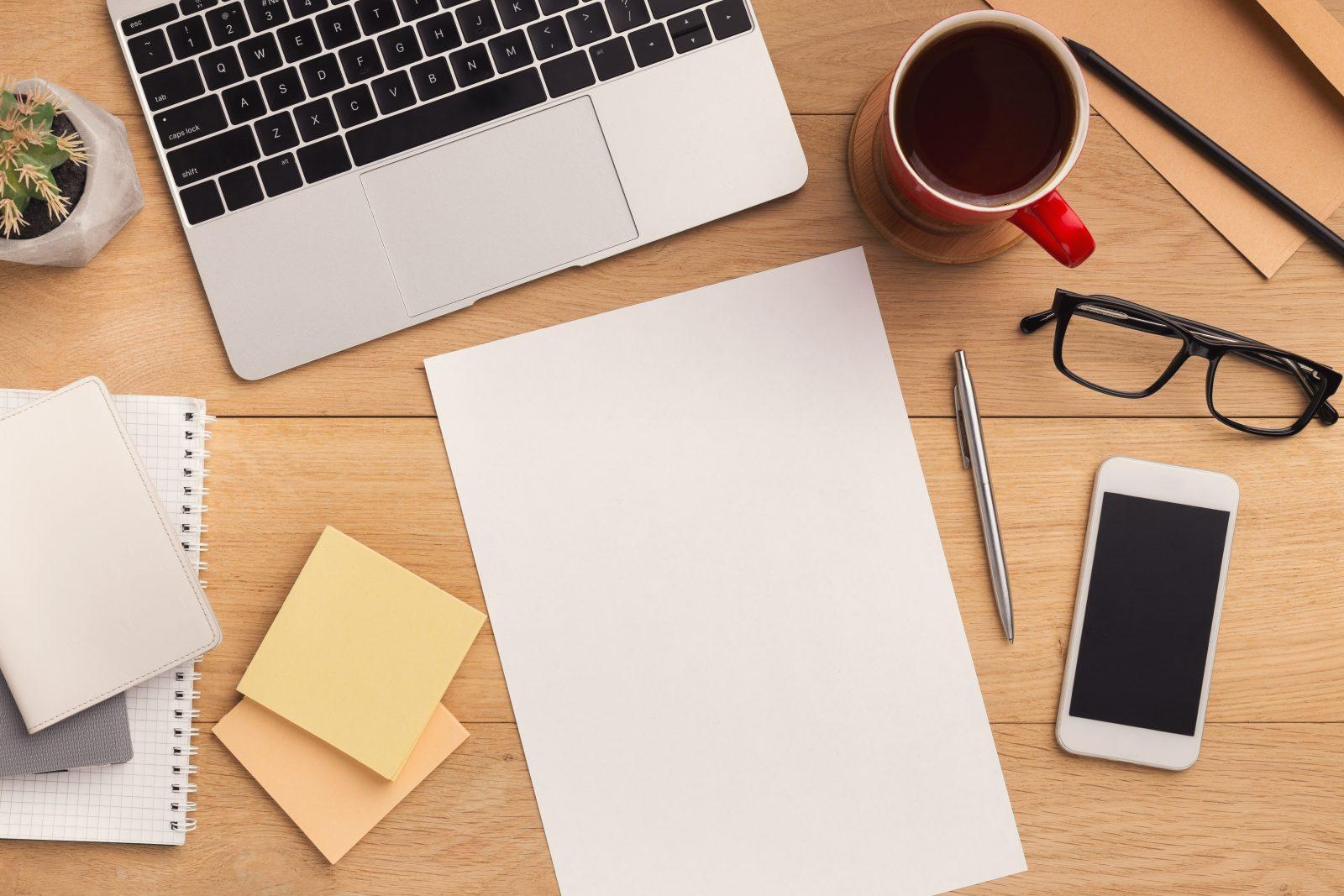 Skrivbord med dator, telefon, kaffekopp och glasögon. Lite post-it-lappar och pennor.