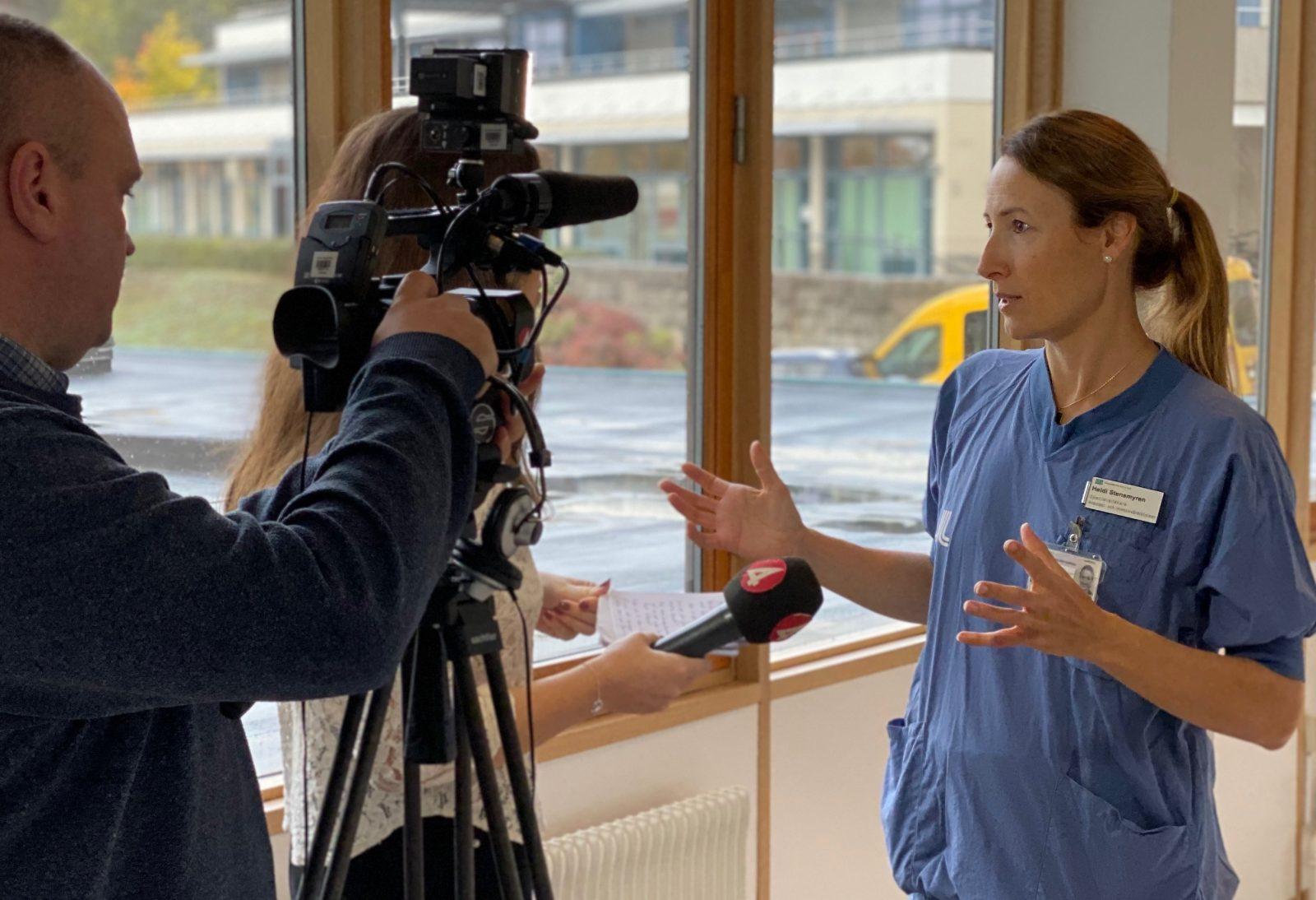 Heidi Stensmyren pratar med journalist framför en kamera
