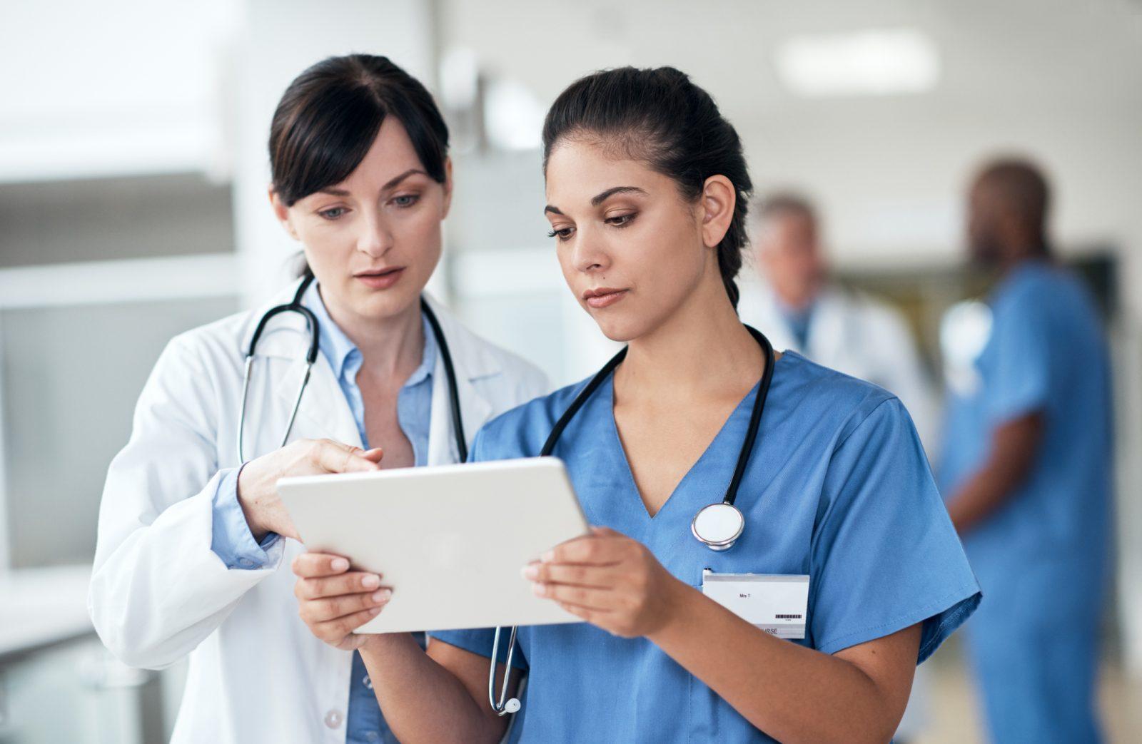 två kvinnliga läkare tittar på samma dokument