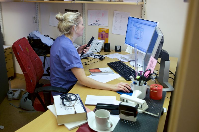Läkare arbetar med administrativa uppgifter vid skrivbord framför en dator
