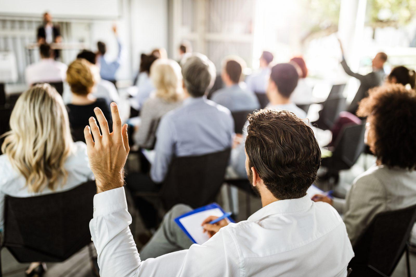 en person räcker upp handen i ett möte