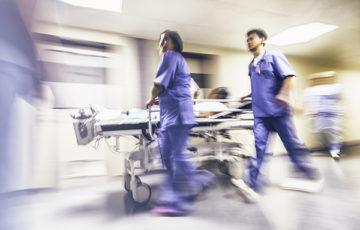 Två läkare genom korridor med sjukhussäng