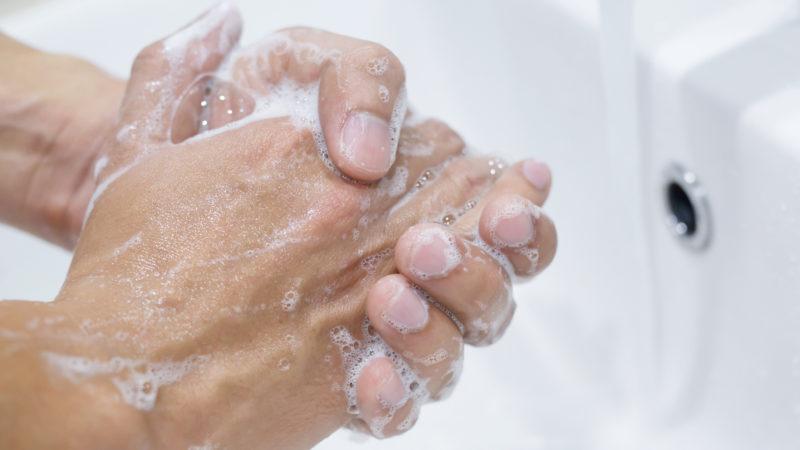 Händer tvättas i handfat under rinnande vatten