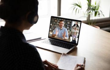 Kvinna sitter framför en laptop, på skärmen syns ett digitalt seminarium