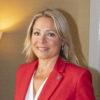 Tina Crafoord, ordförande i Chefsföreningen, bär en röd kavaj och ler mot kameran