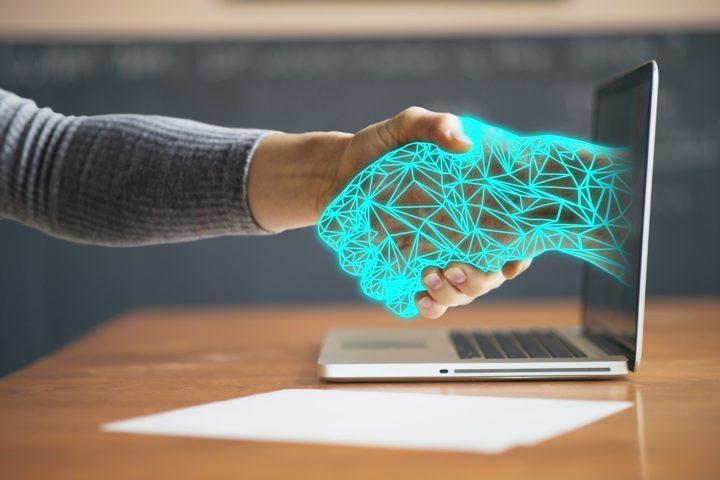 En fysisk hand och en digital hand skakar hand