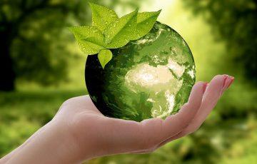 Grön jordglob och klimatsymbol i hand