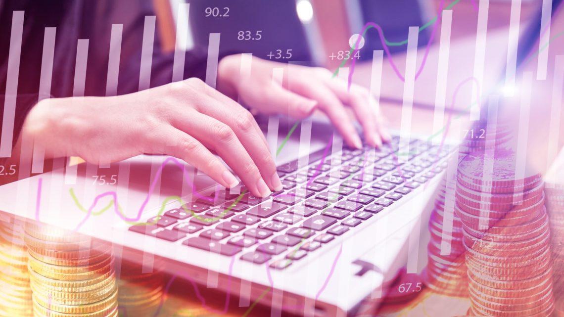 Händer som skriver på en laptop med ekonomiska kurvor och mynt i förgrunden