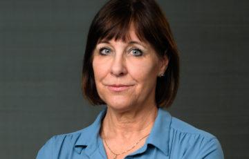 Kvinna med brunt hår och ljusblå blus